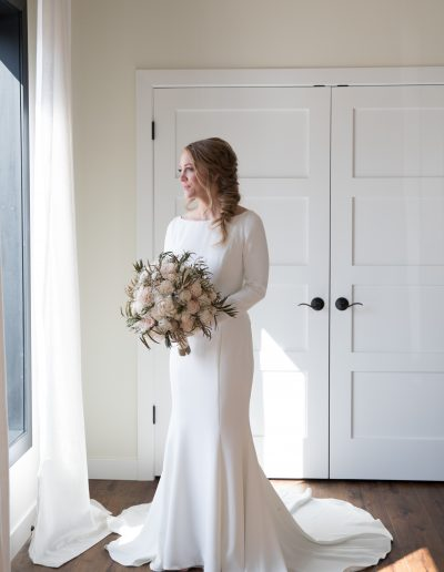 long sleeve wedding dress on bride holding flower bouquet on her wedding day in Wisconsin